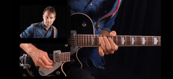 man learning to play guitar with guitar tricks
